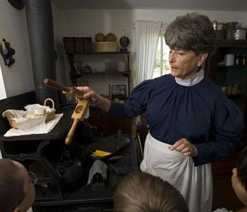 Tour guide shows period kitchenware.