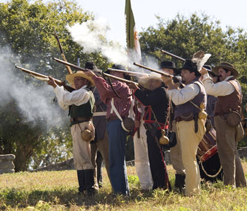 Reenactor soldiers fire their guns.