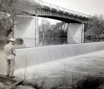 Fisherman by dam below highway bridge