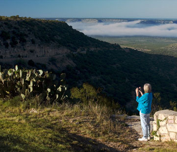 Woman takes a photo of the sprawling vista.