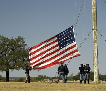 Reenactors raise the US flag.